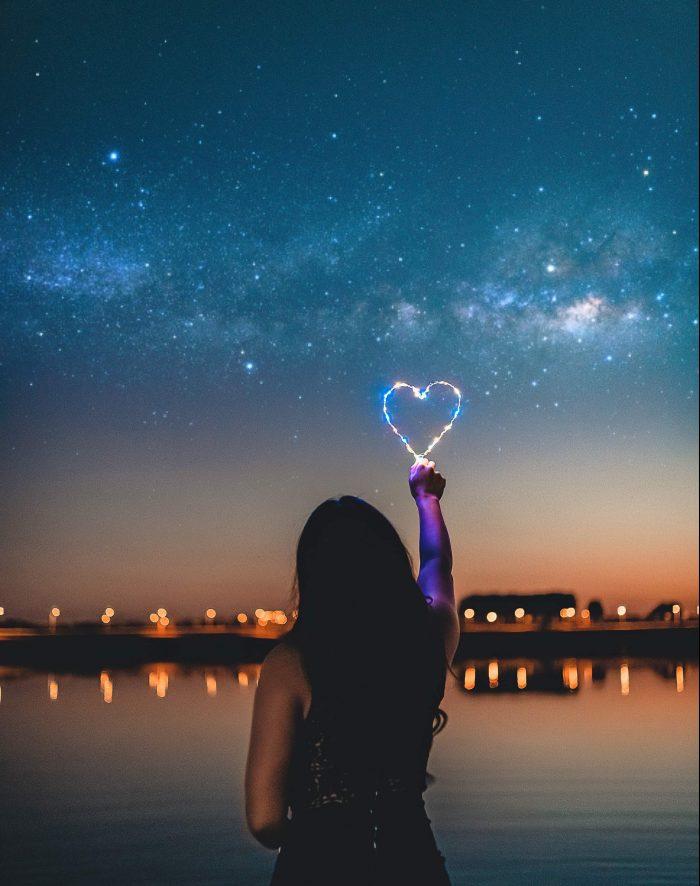 woman holding heart-shaped lights