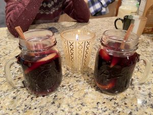 Two glass footed mugs filled with mulled wine and cinnamon sticks, with a lit glass holiday candle in the center