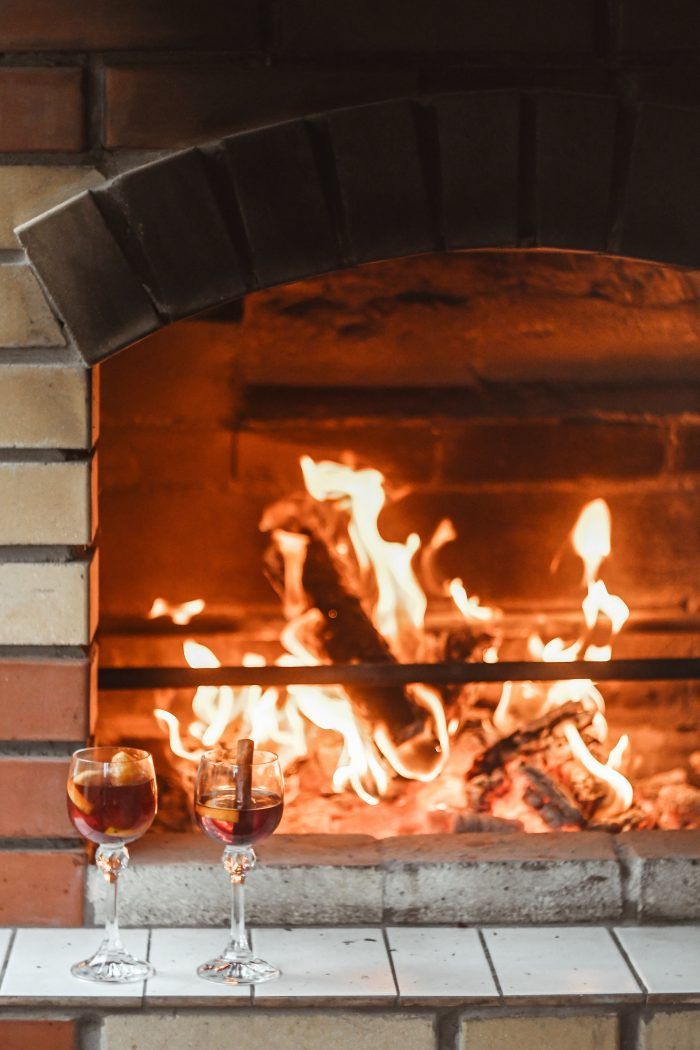 A Yule log burns in a brick fireplace with two glass goblets of mulled wine set in front of it.